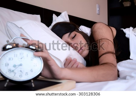 Sleeping young woman turning off the alarm clock in the morning - stock photo