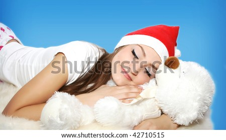 Sleeping young woman with teddy bear in santa hat