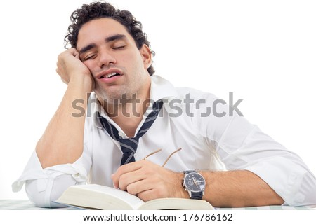 sleepy and tired man with glasses in white shirt and tie sitting with book - stock photo