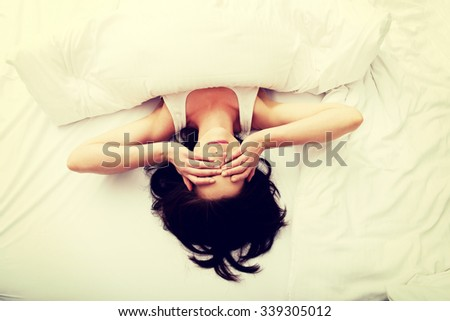 Sleepy brunette woman waking up and rubbing her eyes.