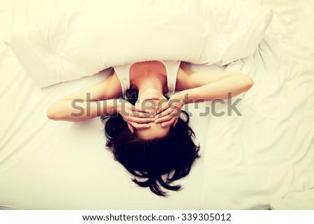 Sleepy brunette woman waking up and rubbing her eyes. - stock photo