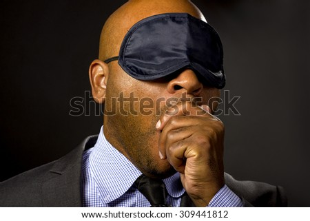 Sleepy businessman wearing an eye mask because of jet lag.  The corporate entrepreneur is sleepy or an insomniac who sleeps during work time.