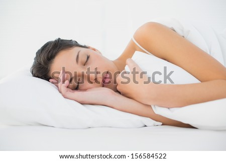 Sleepy casual brunette lying in her bed in bright bedroom - stock photo