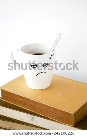 sleepy face coffee cup on stack of books - stock photo