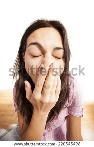 sleepy girl yawns and covers her mouth with her hand - stock photo