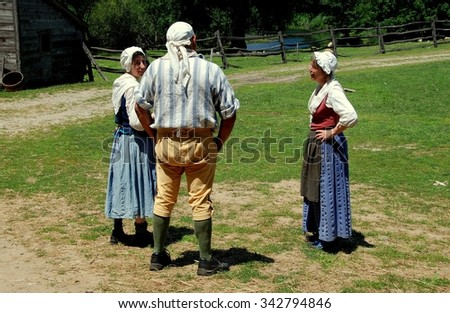 Sleepy Hollow, NY - July 9, 2009:  Interpreters in 18th century clothing pause to chat on farm lands at c. 1750 Philipsburg Manor