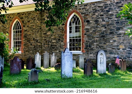 SLEEPY HOLLOW, NY:  Old burial ground stones and 1685 Old Dutch Church of Sleepy Hollow - stock photo