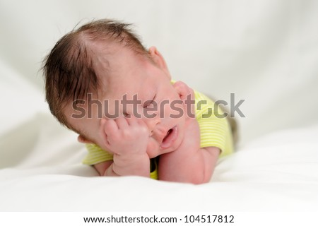 Sleepy Infant Boy. One month old infant with his head in his hands as if he is exhausted. Shallow DOF. - stock photo