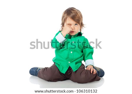 Sleepy little kid, 2 years old boy, sitting on the floor  and rubbing his eyes, wearing shirt and jeans. High resolution image isolated on white background with copy space. Studio shot.