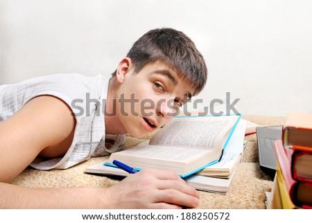 Sleepy Teenager awake on the Sofa with the Books - stock photo