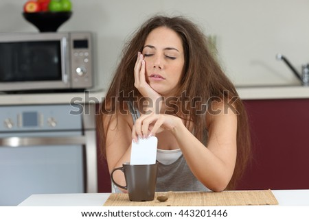 Sleepy tired girl with a bad wake up stirring coffee with the phone sitting in the kitchen at home - stock photo