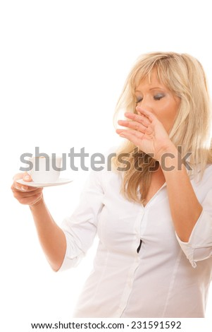 Sleepy tired mature business woman yawning covering mouth with hand holding cup of coffee isolated - stock photo