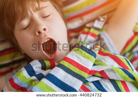 Sleepy yawning teenager girl in bed under a striped colored blanket - stock photo
