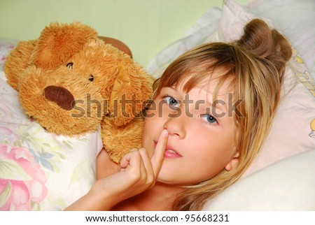 sleepy  young girl lying in bed with mascot asking to be silent