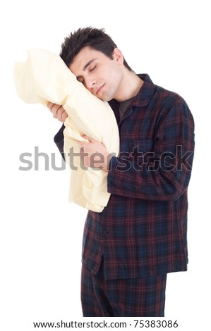 sleepy young man in pajamas holding pillow isolated on white background