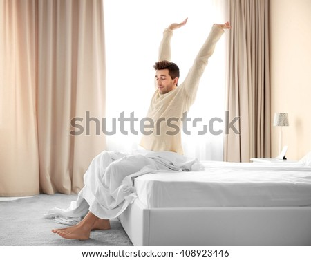 Sleepy young man stretching on bed. - stock photo