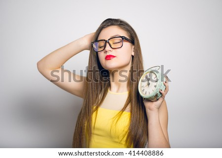 Sleepy young woman with a retro alarm clock in yellow clothes close-up isolated - stock photo