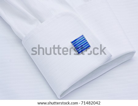 Sleeve of a white shirt with a dark blue cuff link close up - stock photo
