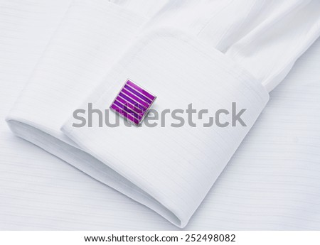 Sleeve of a white shirt with a lilac cuff link - stock photo