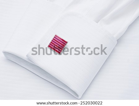 Sleeve of a white shirt with a red cuff link - stock photo