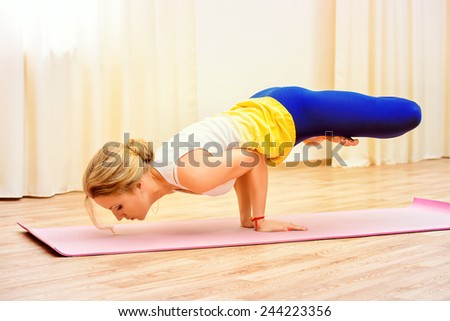 Slender athletic girl doing yoga exercises indoor. Professional trainer. - stock photo