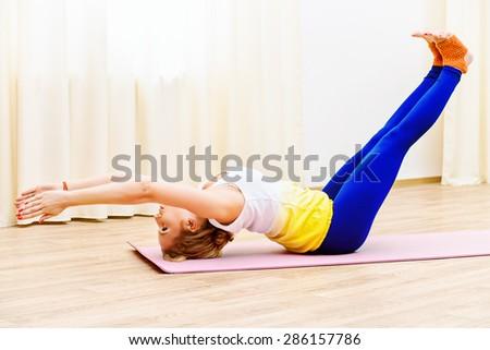Slender athletic girl doing yoga exercises indoor. Professional trainer. - stock photo