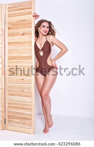 Slender attractive girl measures the swimsuit in a store. Shopping. Preparation for the beach season. - stock photo