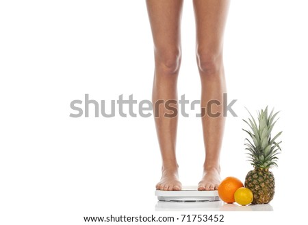 slender beautiful female feet standing on scales in an environment of tropical fruit on a white background. Dietary concept - stock photo