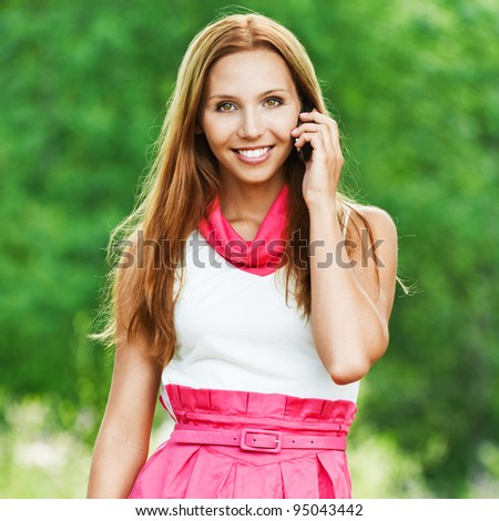 slender, beautiful young woman in white-pink dress standing talking on cell phone on green park - stock photo