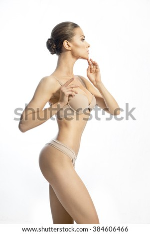 Slender charming woman in a beige lingerie on the white background