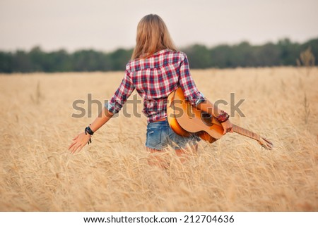 slender girl with a guitar in a wheat field. - stock photo