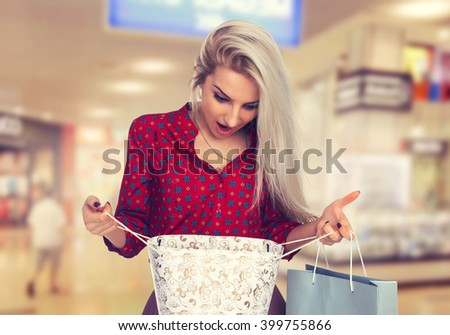 Slender girl with shopping bags in the shopping center. Beauty Woman with Shopping Bags in Shopping Mall. Shopper. Sales. Shopping Center - stock photo
