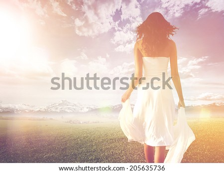 Slender long-haired woman wearing white summer dress while walking on a green meadow towards a bright and sunny horizon, under a dramatic sky, shot from behind, in high-key - stock photo