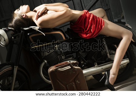 Slender sexual young woman with bright make up in flat red dress and black lingerie sitting on old motorbike in garage in sexy pose on workshop background, horizontal picture - stock photo