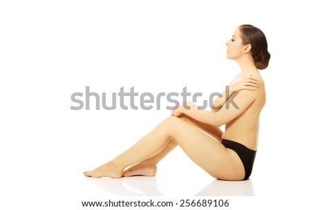 Slender woman in panties sitting on the floor - stock photo