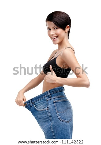 Slender woman wearing enormous jeans, isolated on white - stock photo