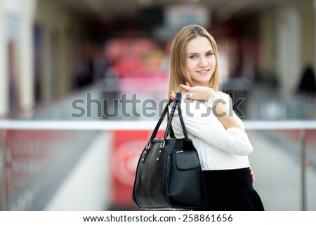 Slender young female model dressed in black and white stylish outfit holding leather handbag wearing matching wristwatch, posing, copyspace