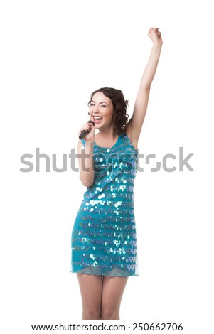 Slender young female talent in short sparkling blue dress, having fun, singing karaoke with emotions, dedication, holding microphone, isolated on white background - stock photo