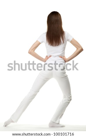 Slender young woman doing sport exercises; rear view on white background - stock photo