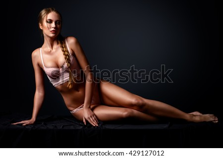Slender young woman in a sexual pink lingerie lying on a floor over black background.