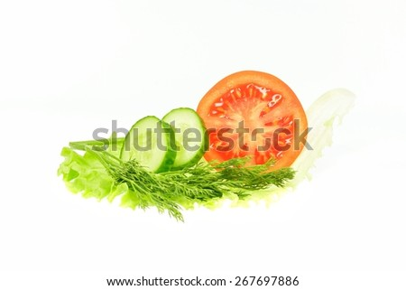 Slice cucumber dill tomato half on a piece of lettuce on a white background - stock photo