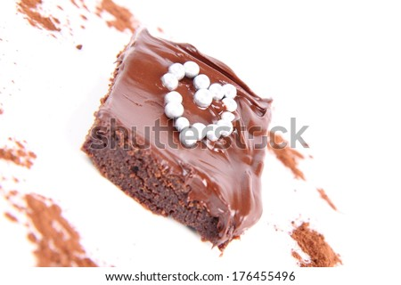 Slice of a brownie covered with chocolate and decorated with heart shape - stock photo