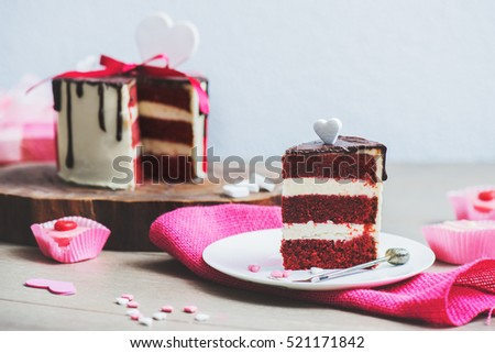 Slice of a red velvet cake with heart shaped decoration on the pink sackcloth
