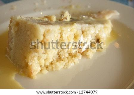 Slice of apple crumble with custard on plate