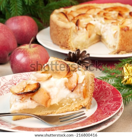Slice of apple pie with cream filling on plate, fruits and christmas decorations in background, rustic stile