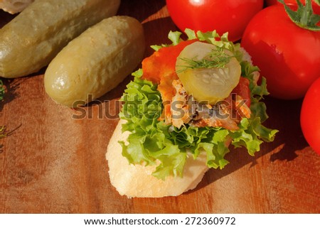 Slice of baguette with Herring fillets in tomato sauce, garnished with lettuce, onion, tomato and pickles on a wooden board - stock photo