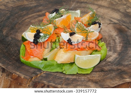 Slice of baguette with smoked salmon, garnished with egg, orange, lemon and caviar on a plate - stock photo