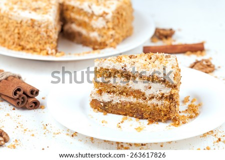 Slice of baked easter carrot cake with raisins and walnut on white background