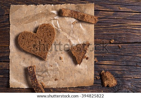 Slice of bread in a heart shape on crumpled paper is located on an old wooden table, top view. Conceptual photo. - stock photo