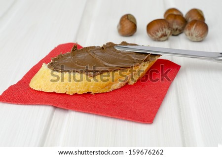 slice of bread smeared with chocolate and hazelnut cream on a red napkin - stock photo